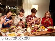 Купить «friends with smartphones having christmas dinner», фото № 29067293, снято 17 декабря 2017 г. (c) Syda Productions / Фотобанк Лори