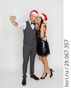 Купить «couple in santa hats aking selfie at christmas», фото № 29067357, снято 15 декабря 2017 г. (c) Syda Productions / Фотобанк Лори