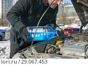 Купить «Man filling a windshield washer tank of a car by antifreeze on busy Moscow street in winter», фото № 29067453, снято 18 марта 2018 г. (c) Георгий Дзюра / Фотобанк Лори