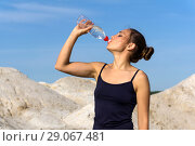 Young slender athletic girl drinks water from a plastic bottle after playing sports outdoors. Стоковое фото, фотограф Евгений Харитонов / Фотобанк Лори