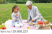 Купить «grandmother and granddaughter at picnic in park», видеоролик № 29068221, снято 24 августа 2018 г. (c) Syda Productions / Фотобанк Лори