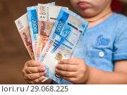 Купить «Маленький мальчик держит в руках бумажные банкноты», эксклюзивное фото № 29068225, снято 10 сентября 2018 г. (c) Игорь Низов / Фотобанк Лори