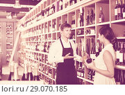 Купить «Seller helping woman customer with bottle of wine», фото № 29070185, снято 20 октября 2018 г. (c) Яков Филимонов / Фотобанк Лори
