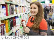 Купить «Женщина с флаконом шампуня в отделе косметики в крупном гипермаркете», фото № 29070565, снято 14 февраля 2014 г. (c) Кекяляйнен Андрей / Фотобанк Лори
