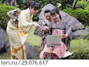 Купить «Три девушки в японском кимоно смотрят в ноутбук и смеются», фото № 29076617, снято 27 марта 2011 г. (c) Александр Гаценко / Фотобанк Лори
