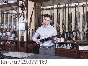 Купить «Handsome adult male owner of hunting shop offering rifle», фото № 29077169, снято 11 декабря 2017 г. (c) Яков Филимонов / Фотобанк Лори