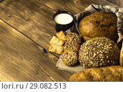 Купить «Food. Rural breakfast. Assortment of fresh bread baked in a bakery, biscuits and a mug with milk on a wooden table background», фото № 29082513, снято 25 августа 2018 г. (c) Светлана Евграфова / Фотобанк Лори