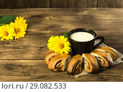 Купить «Food. Baking of confectionery. Fresh baked bakery with poppy seeds and a cup of milk for breakfast on the background of the texture of a wooden table», фото № 29082533, снято 25 августа 2018 г. (c) Светлана Евграфова / Фотобанк Лори