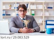 Купить «Businessman with golden cup in the office», фото № 29083529, снято 3 марта 2017 г. (c) Elnur / Фотобанк Лори
