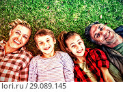 Купить «Happy family lying on the grass in park», фото № 29089145, снято 20 октября 2018 г. (c) Wavebreak Media / Фотобанк Лори
