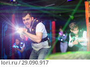 Купить «Emotional guy playing laser tag in colorful beams», фото № 29090917, снято 25 апреля 2018 г. (c) Яков Филимонов / Фотобанк Лори