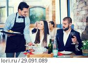 Купить «Waiter male bringing food for smiling couple», фото № 29091089, снято 11 декабря 2017 г. (c) Яков Филимонов / Фотобанк Лори