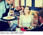 Купить «Waiter male bringing food for male and female», фото № 29091097, снято 11 декабря 2017 г. (c) Яков Филимонов / Фотобанк Лори