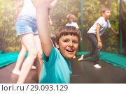 Купить «Happy boy jumping on trampoline with his friends», фото № 29093129, снято 20 мая 2018 г. (c) Сергей Новиков / Фотобанк Лори