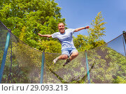 Купить «Girl laughing while jumping on the trampoline», фото № 29093213, снято 20 мая 2018 г. (c) Сергей Новиков / Фотобанк Лори