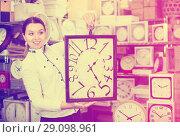 Купить «Woman is choosing new clock for her home in the store.», фото № 29098961, снято 20 декабря 2017 г. (c) Яков Филимонов / Фотобанк Лори