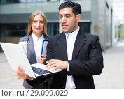 Купить «Couple professionals are examinating project on laptop», фото № 29099029, снято 20 августа 2017 г. (c) Яков Филимонов / Фотобанк Лори
