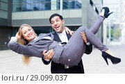 Купить «Boss is carry woman manager on hands because they are satisfied of successful contract», фото № 29099037, снято 20 августа 2017 г. (c) Яков Филимонов / Фотобанк Лори