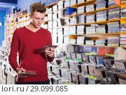 Купить «guy looking on box of DVD movie», фото № 29099085, снято 15 февраля 2018 г. (c) Яков Филимонов / Фотобанк Лори