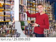 Купить «Man choosing movies on DVD», фото № 29099093, снято 15 февраля 2018 г. (c) Яков Филимонов / Фотобанк Лори