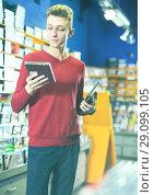 Купить «guy looking on box of DVD movie», фото № 29099105, снято 15 февраля 2018 г. (c) Яков Филимонов / Фотобанк Лори