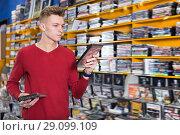 Купить «Glad man choosing movies on DVD at store», фото № 29099109, снято 15 февраля 2018 г. (c) Яков Филимонов / Фотобанк Лори