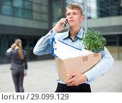 Купить «Young manager is talking phone and searching new job after dismissal», фото № 29099129, снято 15 июля 2017 г. (c) Яков Филимонов / Фотобанк Лори