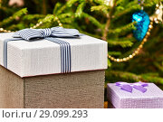Купить «Gift boxes with bows on the lids under a Christmas tree in New Year Eve», фото № 29099293, снято 1 января 2018 г. (c) Георгий Дзюра / Фотобанк Лори