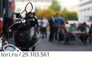 Купить «Motorcycle helmet hanging on the handles of the motorcycle hazy background with people», видеоролик № 29103561, снято 19 сентября 2018 г. (c) Константин Шишкин / Фотобанк Лори