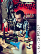 Купить «Male worker working on leather for belt in leather», фото № 29103637, снято 20 октября 2018 г. (c) Яков Филимонов / Фотобанк Лори