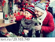 Купить «Male with daughter buying decoration in Christmas market», фото № 29103749, снято 20 сентября 2018 г. (c) Яков Филимонов / Фотобанк Лори