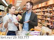 Купить «Smiling couple is choosing meal for home in the food shop», фото № 29103777, снято 4 апреля 2018 г. (c) Яков Филимонов / Фотобанк Лори