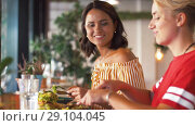 Купить «female friends eating at restaurant», видеоролик № 29104045, снято 23 августа 2018 г. (c) Syda Productions / Фотобанк Лори