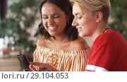 Купить «female friends with smartphone at restaurant», видеоролик № 29104053, снято 23 августа 2018 г. (c) Syda Productions / Фотобанк Лори