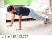 Купить «Young man in pajamas doing morning exercises», фото № 29105737, снято 22 июня 2018 г. (c) Elnur / Фотобанк Лори