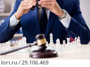 Купить «Young lawyer playing chess to train his court strategy and tacti», фото № 29106469, снято 31 июля 2018 г. (c) Elnur / Фотобанк Лори