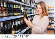 Купить «Female buying bottle of wine», фото № 29111181, снято 11 апреля 2018 г. (c) Яков Филимонов / Фотобанк Лори