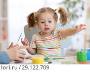 Купить «Cute little toddler girl in striped shirt and pony tails paints in the art class», фото № 29122709, снято 22 сентября 2018 г. (c) Оксана Кузьмина / Фотобанк Лори