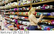 Купить «Young woman looking for interesting cloth in textile shop», видеоролик № 29122733, снято 28 марта 2018 г. (c) Яков Филимонов / Фотобанк Лори