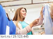 Купить «happy woman choosing clothes at clothing store», фото № 29123445, снято 19 февраля 2016 г. (c) Syda Productions / Фотобанк Лори