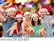 Купить «happy friends in santa hats over festive lights», фото № 29123653, снято 30 июня 2018 г. (c) Syda Productions / Фотобанк Лори