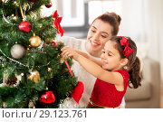happy family decorating christmas tree at home. Стоковое фото, фотограф Syda Productions / Фотобанк Лори