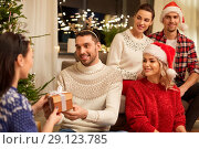 Купить «friends celebrating christmas and giving presents», фото № 29123785, снято 17 декабря 2017 г. (c) Syda Productions / Фотобанк Лори