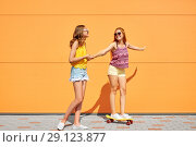Купить «teenage girls riding skateboard on city street», фото № 29123877, снято 19 июля 2018 г. (c) Syda Productions / Фотобанк Лори