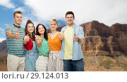 friends showing thumbs up over grand canyon. Стоковое фото, фотограф Syda Productions / Фотобанк Лори