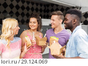 Купить «happy friends with drinks eating at food truck», фото № 29124069, снято 1 августа 2017 г. (c) Syda Productions / Фотобанк Лори