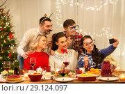 Купить «friends taking selfie at christmas dinner», фото № 29124097, снято 17 декабря 2017 г. (c) Syda Productions / Фотобанк Лори