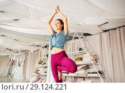 Купить «young woman doing yoga tree pose at studio», фото № 29124221, снято 21 июня 2018 г. (c) Syda Productions / Фотобанк Лори