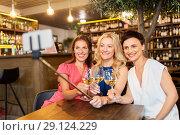 Купить «women taking picture by selfie stick at wine bar», фото № 29124229, снято 25 июня 2018 г. (c) Syda Productions / Фотобанк Лори