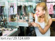Купить «Girl choosing bijouterie in glass showcase in boutique», фото № 29124689, снято 10 декабря 2019 г. (c) Яков Филимонов / Фотобанк Лори